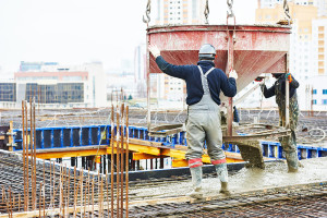 concreting work: construction site worker during concrete pourin