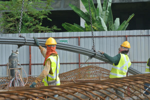 Construction workers using crane to lifting heavy reinforcement